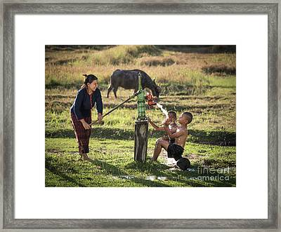 Framed Print featuring the photograph Mother Her Sons Shower Outdoor From Groundwater Pump. by Tosporn Preede