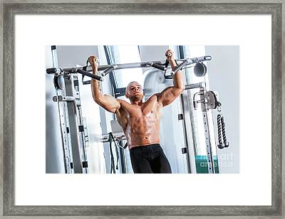 Muscular Strong Man Working Out At A Gym. Framed Print