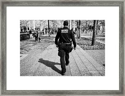 nypd counterterrorism officer walking through the 9/11 memorial plaza New York City USA Framed Print