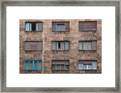 Old European Building With Woman Looking Out Window Framed Print by Aaron Sheinbein