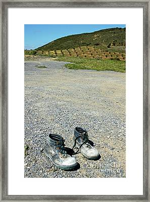Old Pair Of Worn Out Boots Sitting On Stony Asphalt Framed Print by Sami Sarkis
