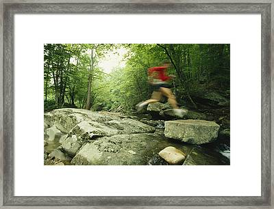 Panned View Of Man Leaping Over Rocky Framed Print by Skip Brown