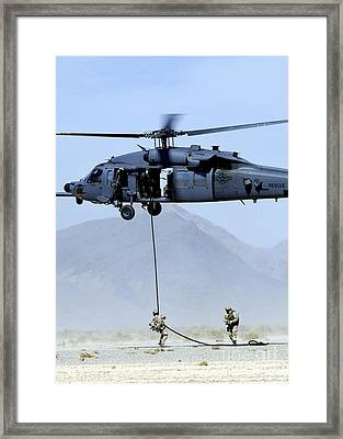 Pararescuemen Descend From An Hh-60 Framed Print by Stocktrek Images