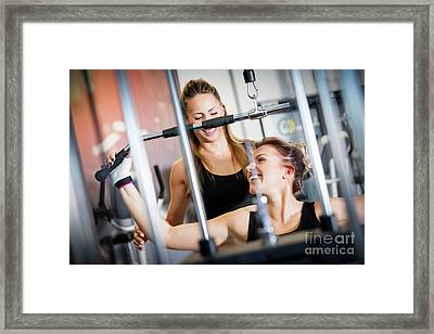 Personal Trainer Helps With Gym Equipment Workout. Framed Print