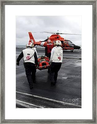 Personnel Carry An Injured Sailor Framed Print by Stocktrek Images