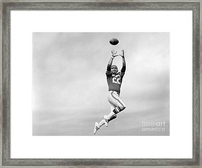 Player Jumping To Catch Football Framed Print