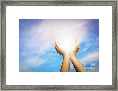 Raised Hands Catching Sun On Blue Sky. Concept Of Spirituality,  Framed Print by Michal Bednarek