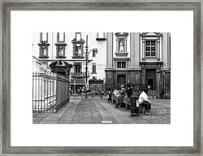 Reading The Paper In Piazza Dante Framed Print by John Rizzuto