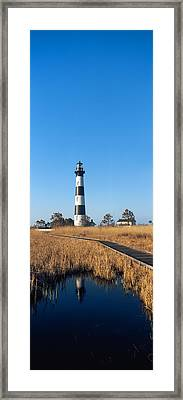 Reflection Of A Lighthouse On Water Framed Print by Panoramic Images