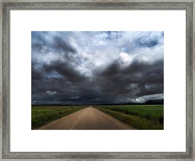 Riding Into Dark Clouds Framed Print by Eric Benjamin