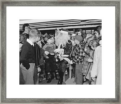Santa Surrounded By Children Framed Print by Underwood Archives