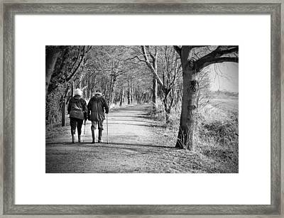 Senior Couple Walking Through The Woods Framed Print