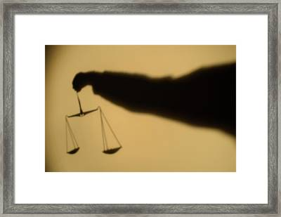 Shadow Of A Person's Arm Holding Out The Scales Of Justice Framed Print by Sami Sarkis