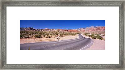 Side Profile Of A Person Cycling Framed Print by Panoramic Images