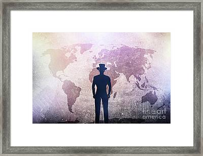 Silhouette Of A Man In Hat Standing In Front Of World Map On Grunge Concrete Wall Framed Print
