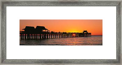 Silhouette Of Huts And A Pier At Dusk Framed Print