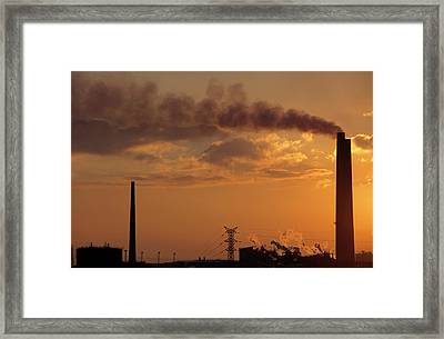 Silhouetted Smoking Chimney At Sunset Framed Print by Sami Sarkis