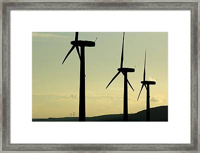 Silhouetted Wind Turbines Against A Cloudy Sky Framed Print by Sami Sarkis