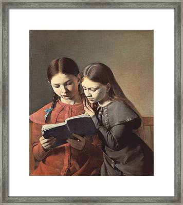 Sisters Reading A Book Framed Print by Carl Hansen