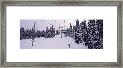 Ski Lift Passing Over A Snow Covered Framed Print
