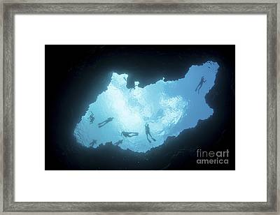 Snorkelers Swim Above A Blue Hole Framed Print by Ethan Daniels