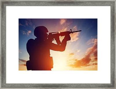 Soldier Shooting With His Rifle At Sunset Framed Print by Michal Bednarek
