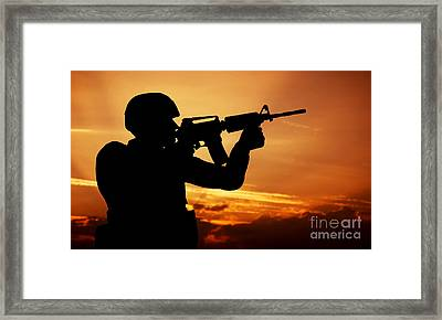 Soldier Shooting With His Weapon At Sunset Framed Print by Michal Bednarek