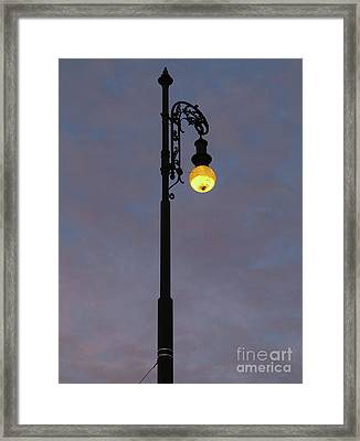 Framed Print featuring the photograph Street Lamp Shining At Dusk by Michal Boubin