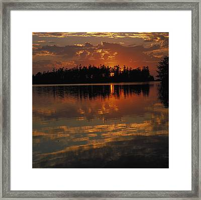 Sunset Behind The Trees On A Lake Framed Print