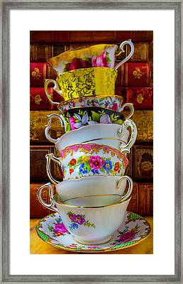 Tea Cups Stacked Against Old Books Framed Print