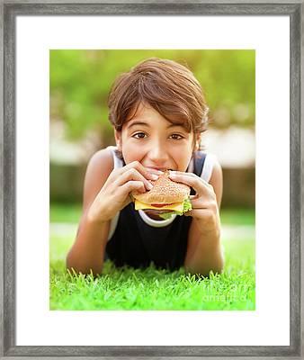 Teen Boy Eating Burger Outdoors Framed Print