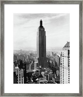 The Empire State Building Under Construction Framed Print by Jon Neidert