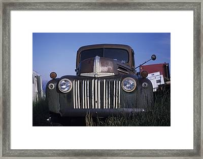 The Ruins Of A Car Sit In An Open Field Framed Print