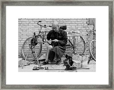 Framed Print featuring the photograph The Shoe Mender by Nigel Fletcher-Jones
