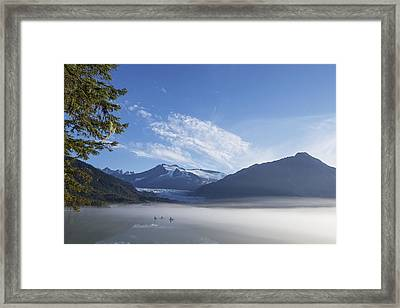 Three Kayakers Paddle The Shoreline Framed Print by John Hyde
