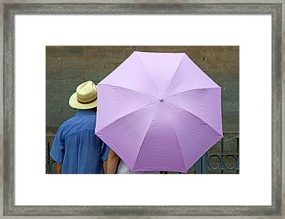 Tourist Looking At A Wall While Sheltering Under An Umbrella Framed Print