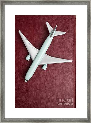 Framed Print featuring the photograph Toy Airplane Over Red Book Cover by Edward Fielding