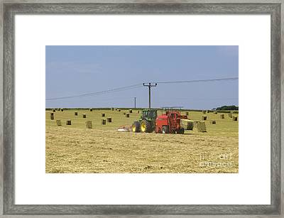 Tractor Bailing Hay In A Field At Harvest Time Framed Print by Andy Smy