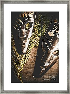 Tribal Masks With Ferns On Wooden Table Framed Print