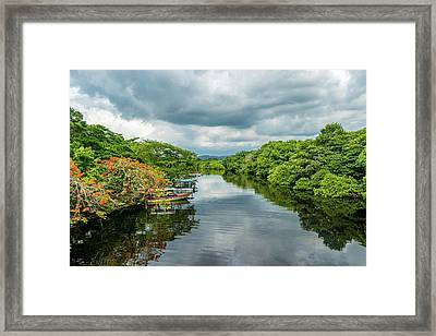 Cloudy Skies Over The River Framed Print