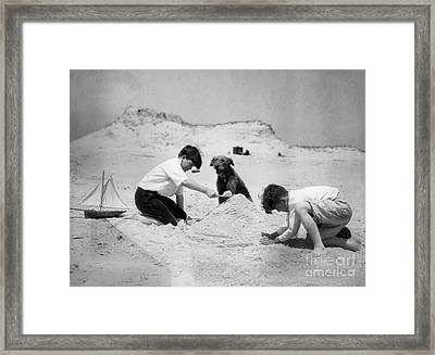 Two Boys And Dog Playing On Beach Framed Print by H. Armstrong Roberts/ClassicStock