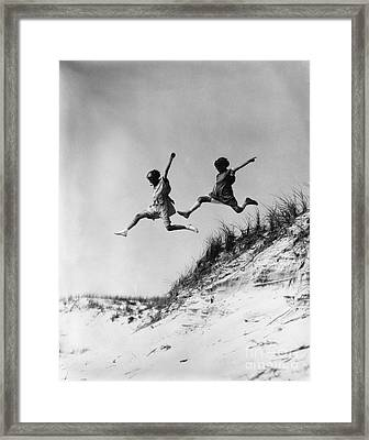 Two Girls Leaping Off Sand Dune Framed Print by H. Armstrong Roberts/ClassicStock
