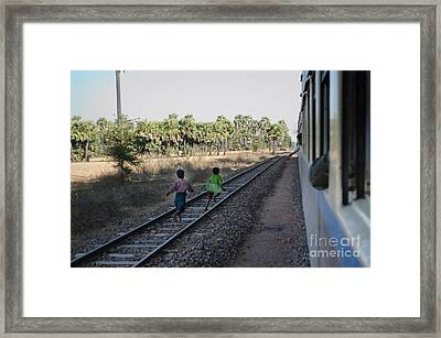 Framed Print featuring the photograph Two Kids Run Along And Follow Train In Burma by Jason Rosette