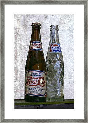 Two Pepsi Bottles On A Table Framed Print