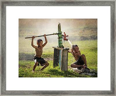 Two Young Boy Rocking Groundwater Bathe In The Hot Days. Framed Print by Tosporn Preede
