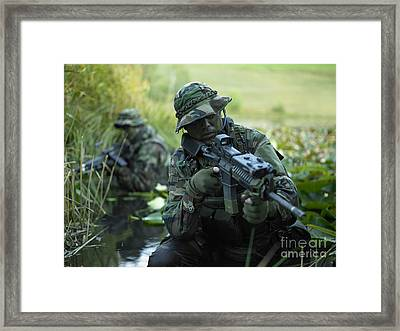 U.s. Navy Seals Cross Through A Stream Framed Print by Tom Weber