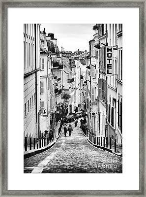 Vers Le Haut De La Rue Framed Print by John Rizzuto