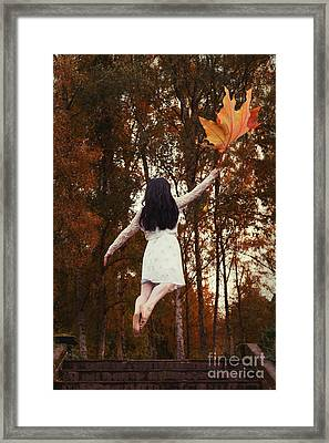 Woman Floating Away With Autumn Leaf Framed Print by Amanda Elwell