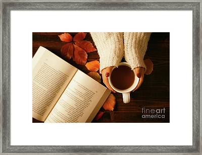 Woman Hands Holding Teacup And Opened Book Seen From Above Framed Print by Luigi Morbidelli