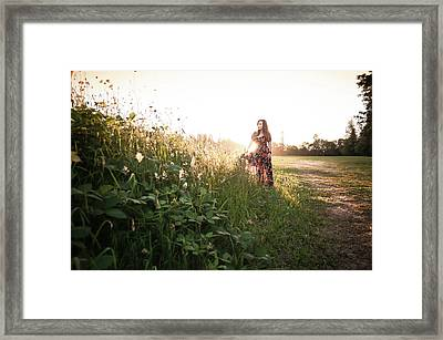 Woman Standing Among Wildflowers In Meadow At Sunset Framed Print by Bradley Hebdon